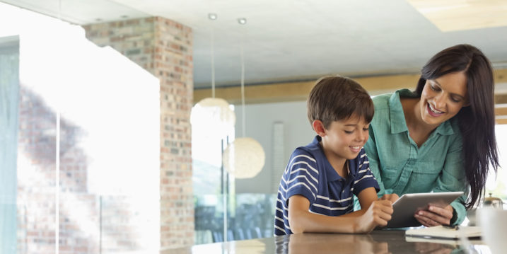 Mother and son using tablet computer in kitchen