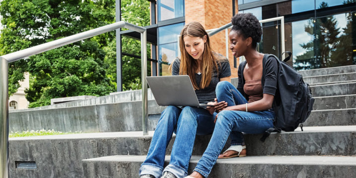 Two young female college students sitting on steps in front of a university building, looking at a laptop screen together.