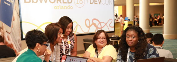 Several women gathered around a laptop in front of the BbWorld and DevCon logo