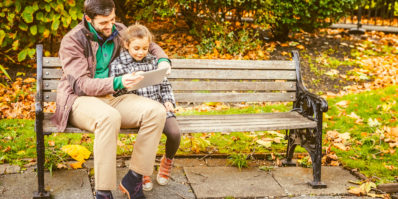 Father and Daughter with Digital Tablet, Park in Autumn.