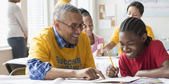 Volunteers tutoring students in classroom