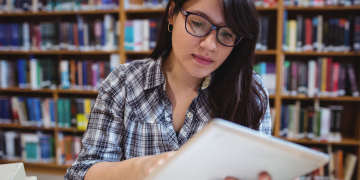 Female student using digital tablet in library
