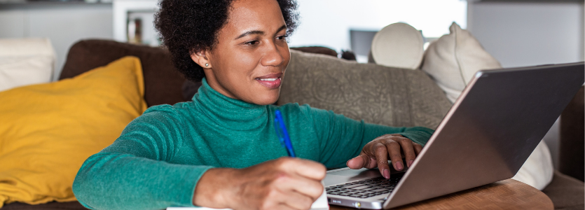 Woman sitting comfortably at home and working on the laptop