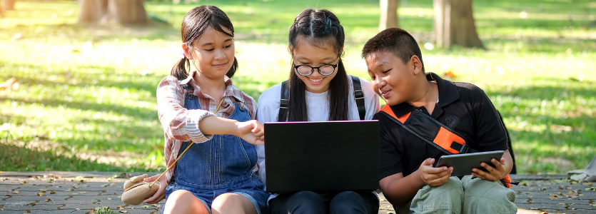 Summer school concept,Asian children are playing laptop computer in the park.